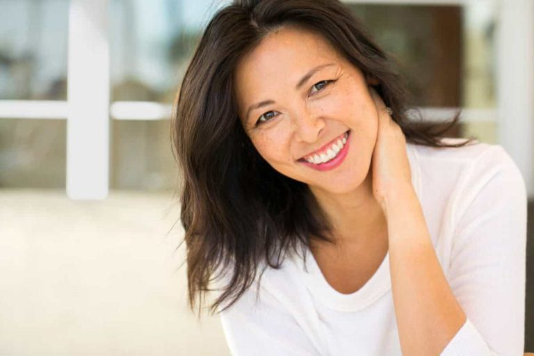 woman smiling with a hand behind her neck