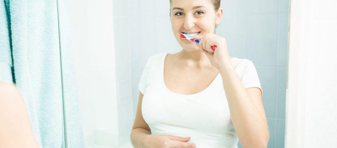 Pregnant woman brushing teeth